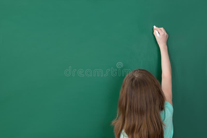 在黑板的女孩文字 库存图片