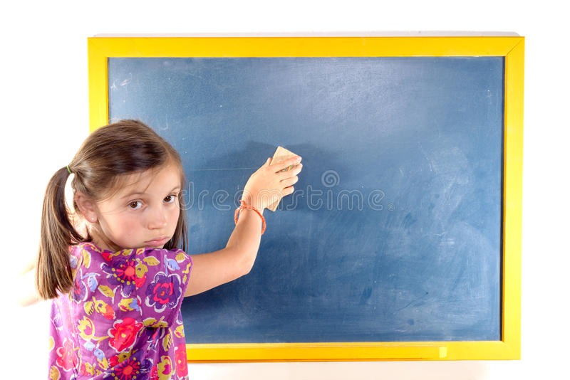 在黑板的女小学生删掉 库存照片