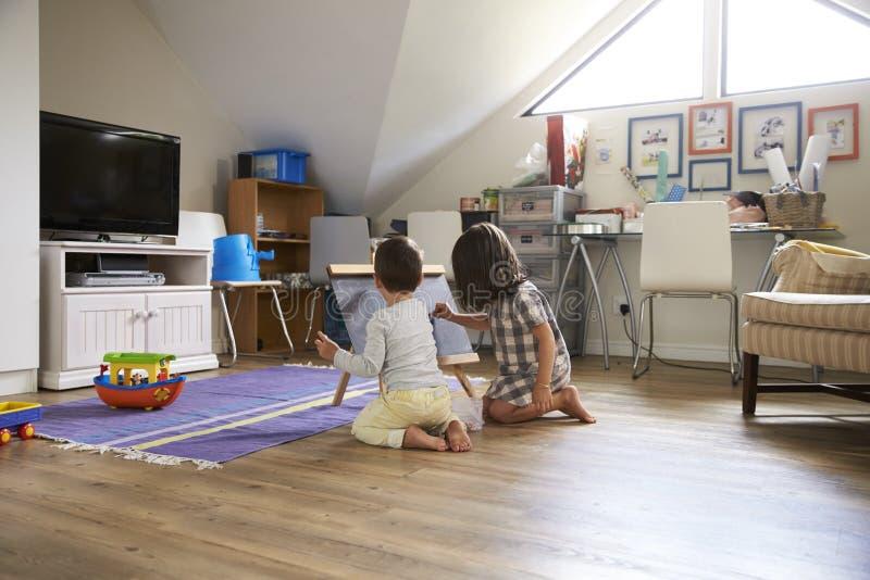 在黑板的男孩和女孩图画在游戏室 库存图片