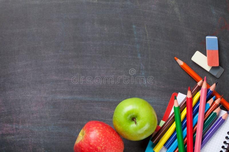 在黑板背景的学校用品 免版税库存图片