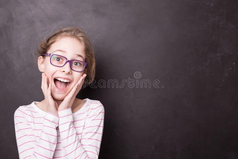 在黑板黑板的激动的白肤金发的儿童女孩孩子 免版税库存图片