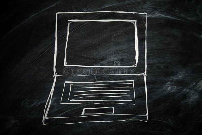 在黑板画的膝上型计算机 免版税库存图片