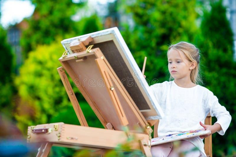 绘在画架的可爱的小女孩一幅画户外 免版税库存照片