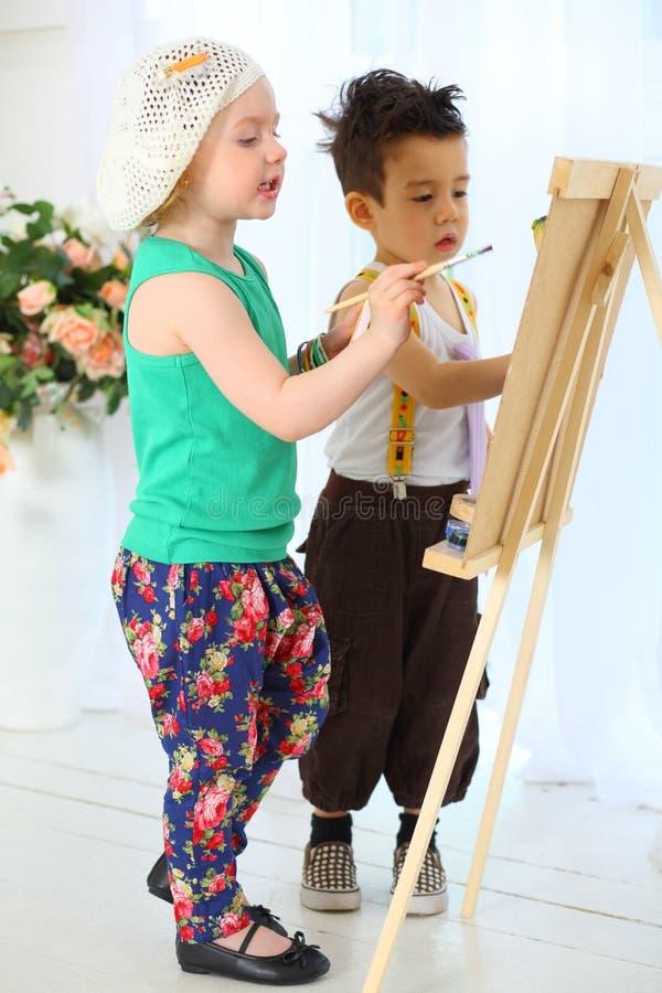 在画架的女孩和男孩油漆 免版税库存照片