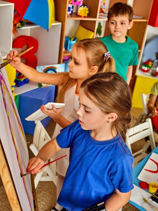 绘在画架的孩子手指 小组与老师的孩子 免版税库存照片