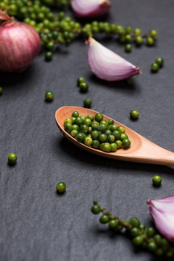 在黑桌上的新鲜蔬菜 红洋葱圆环和绿色peppe 免版税库存图片