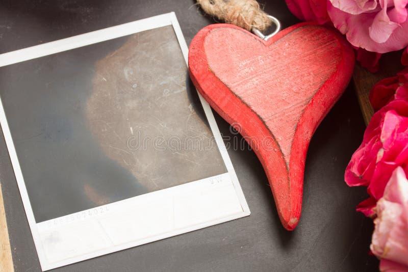 在黑桌上的空白瞬时与心脏 免版税库存照片