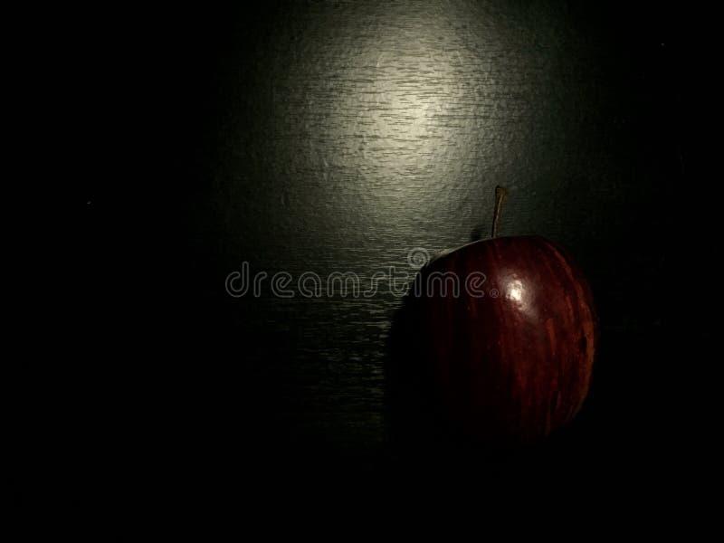 在黑桌上的苹果计算机在暗影掩藏 图库摄影