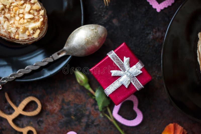 在黑桌的红色箱子礼物与甜沙漠 免版税库存图片