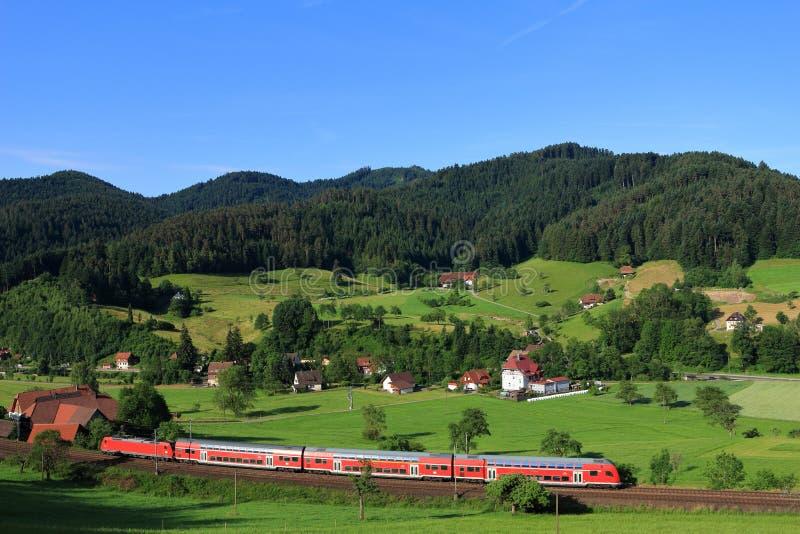 在黑森林风景的红色火车 库存照片
