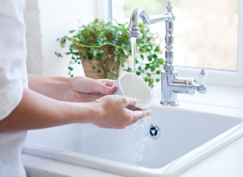 在水槽的妇女洗涤的盘 库存图片