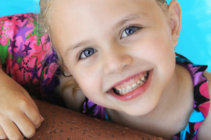 在水池的一点白肤金发的女孩游泳在夏天 免版税图库摄影