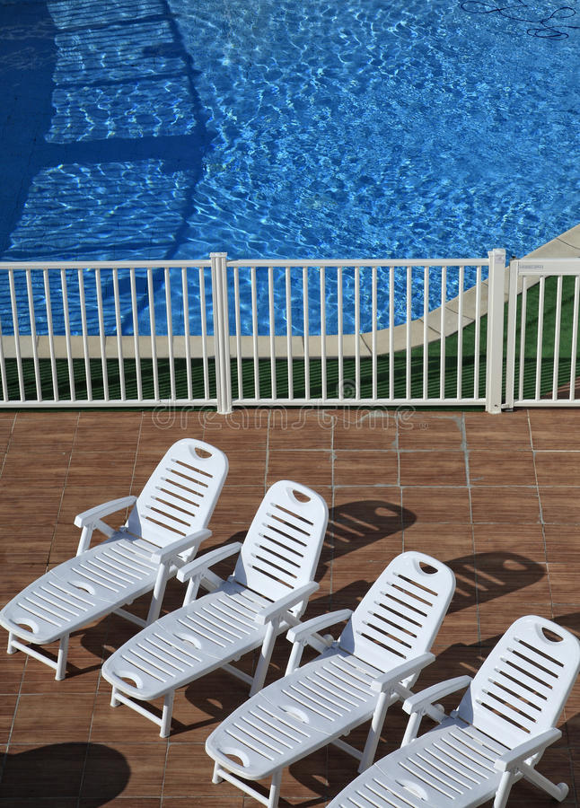 在水池的四把可躺式椅 免版税图库摄影