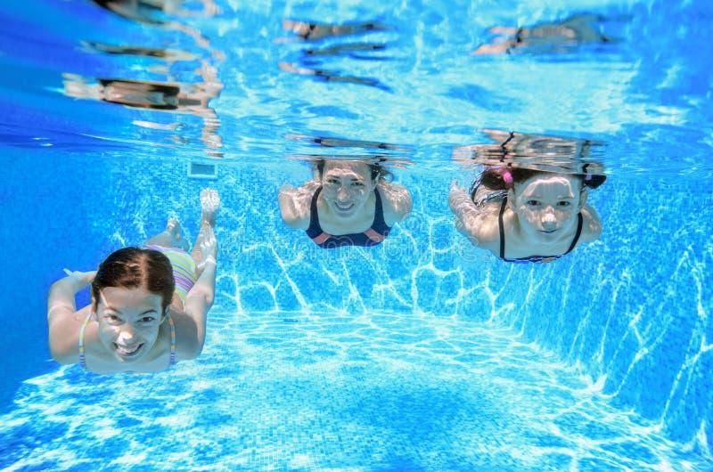 在水池的家庭游泳在水下,愉快的活跃母亲和孩子有乐趣、健身和体育与孩子 免版税库存照片