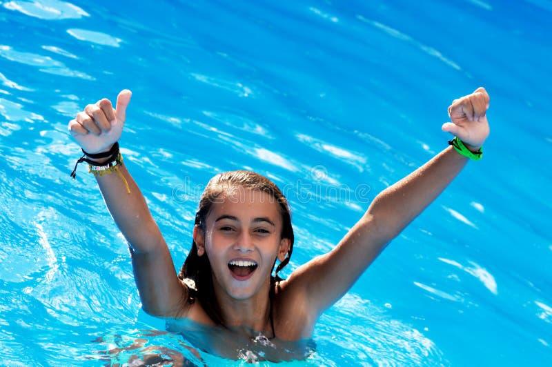 在水池的愉快的女孩游泳 库存照片