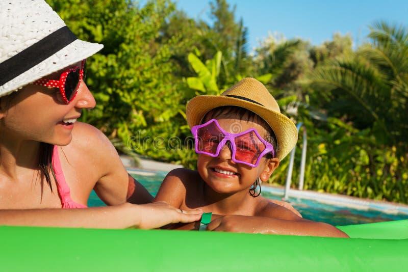 在水池的愉快的母亲和男孩佩带的太阳镜 库存照片
