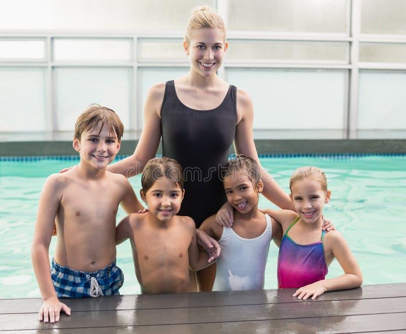 在水池的逗人喜爱的游泳类与教练 库存图片