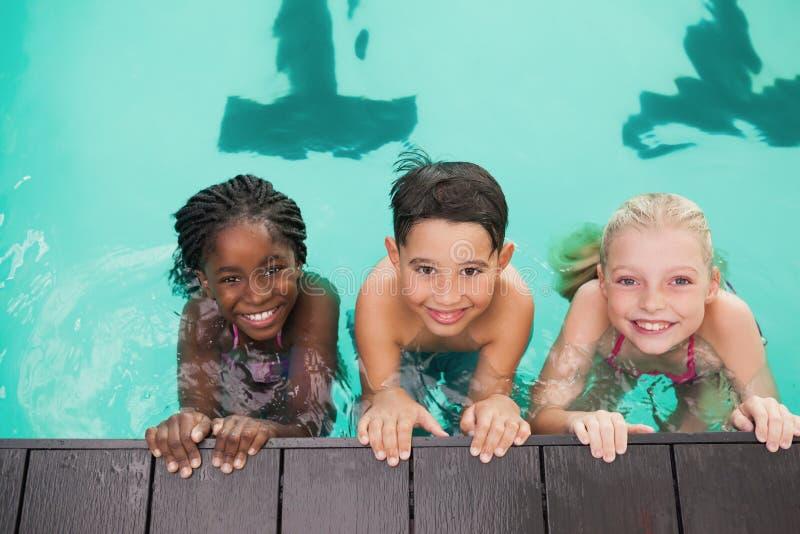 在水池的逗人喜爱的游泳类与教练 免版税图库摄影