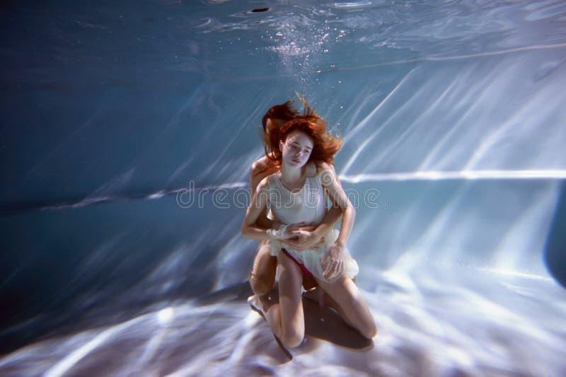 在水池的水中用最纯净的水 拥抱爱的夫妇 爱和严紧的感觉 软绵绵地集中 库存图片
