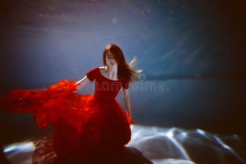 在水池的水中用最纯净的水 猩红色礼服和流动的头发的美丽的女孩 库存照片