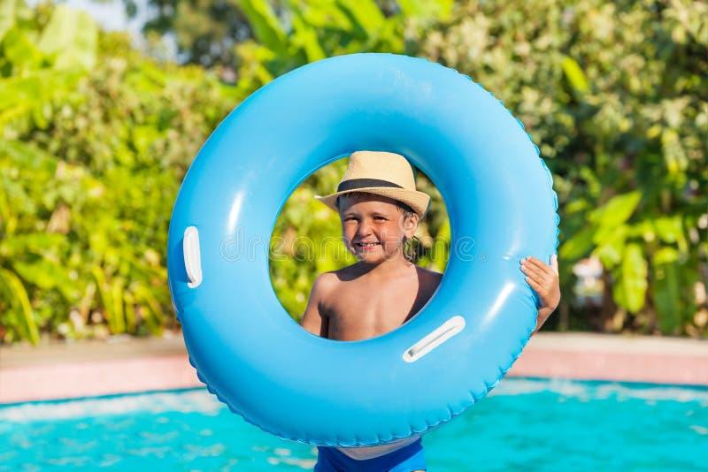 在水池附近拿着可膨胀的圆环的帽子的男孩 免版税库存照片