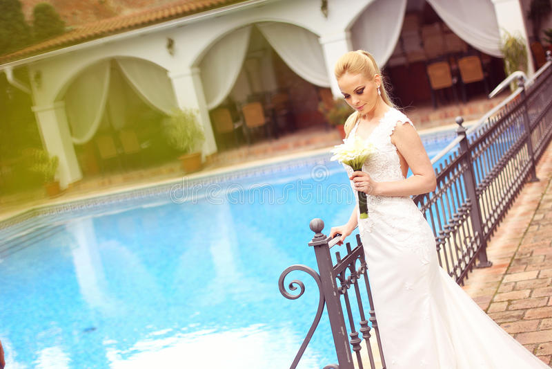在水池附近的美丽的新娘 免版税库存照片