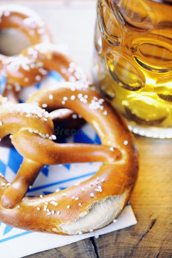 在巴法力亚餐巾的椒盐脆饼和啤酒 免版税库存照片