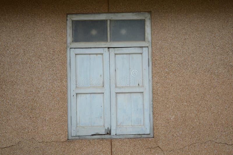 在水泥墙壁上的木窗口 免版税库存照片