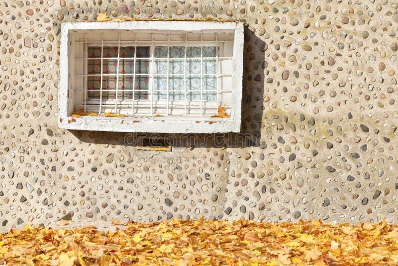 在水泥石墙壁上的老窗口有秋季叶子的 图库摄影