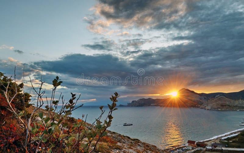 在黑海的克里米亚半岛海岸的红色日落一个安静的海湾的 库存照片