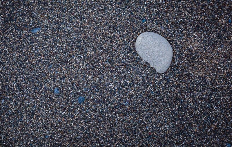 在黑火山的沙子的白色石头在海滩 库存图片