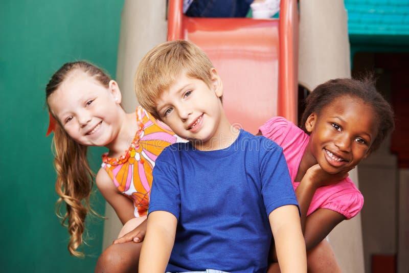 在幻灯片的愉快的孩子在幼儿园 库存照片