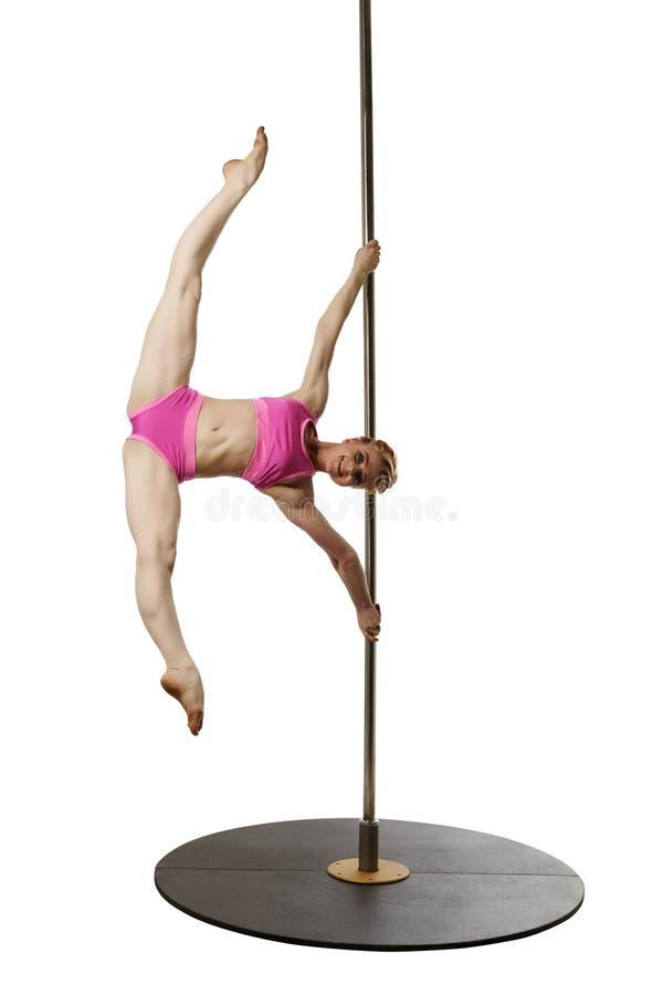 在锻炼期间的微笑的体操运动员姿势在杆 免版税库存照片