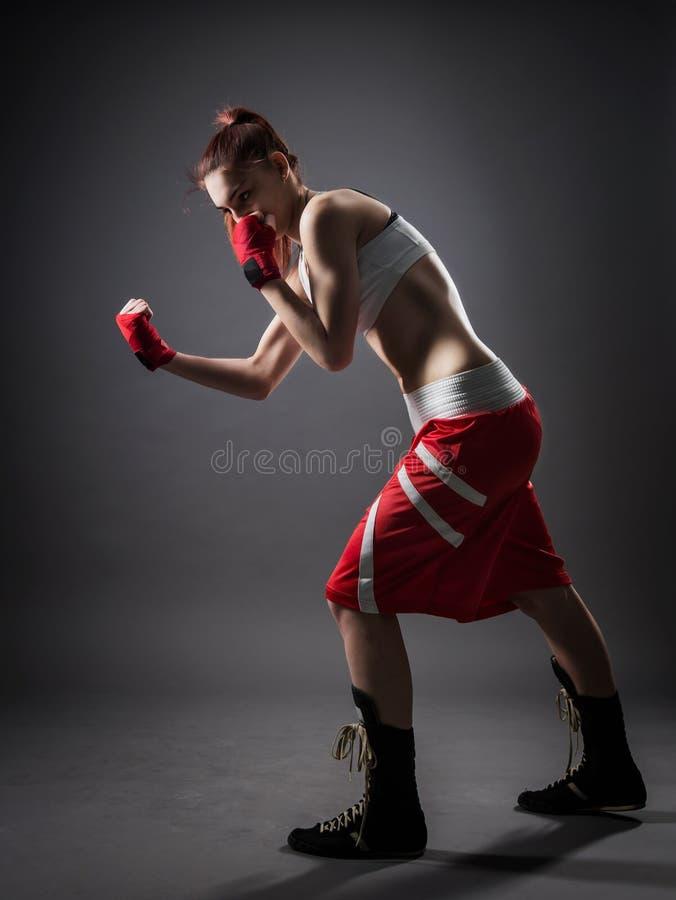 在锻炼灰色背景期间的拳击妇女 库存图片