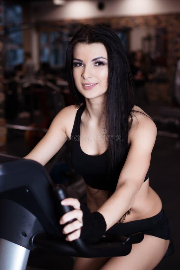 在锻炼脚踏车的肌肉少妇佩带的运动服训练在健身房 强烈的心脏锻炼 免版税库存照片
