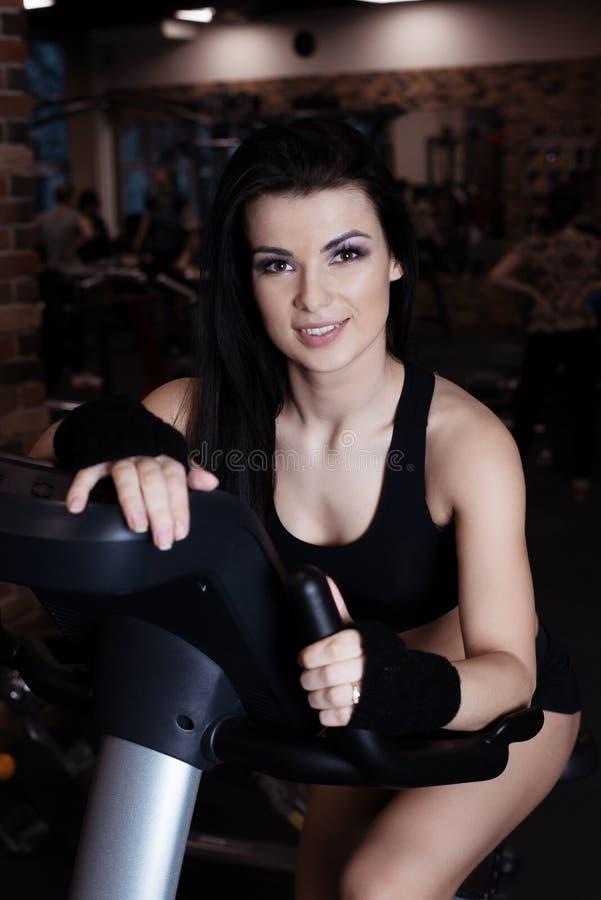 在锻炼脚踏车的肌肉少妇佩带的运动服训练在健身房 强烈的心脏锻炼 免版税库存图片