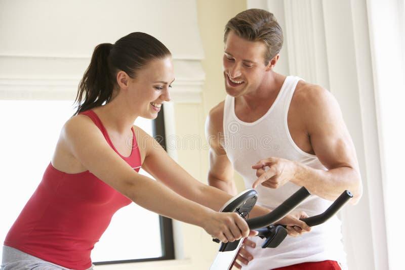 在锻炼脚踏车的年轻夫妇 库存图片