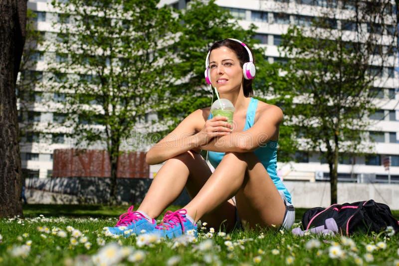 在锻炼以后的健身妇女饮用的戒毒所圆滑的人 免版税库存图片