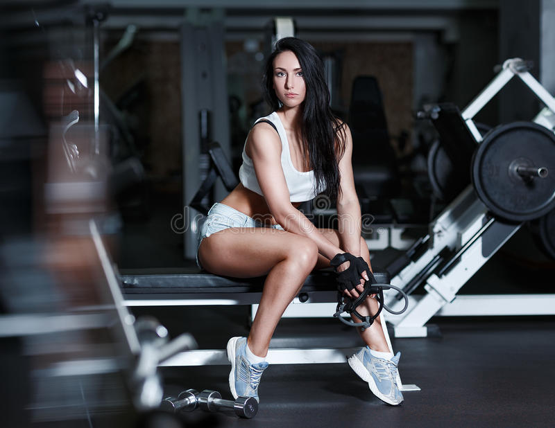 在锻炼以后的年轻性感的妇女在健身房 图库摄影