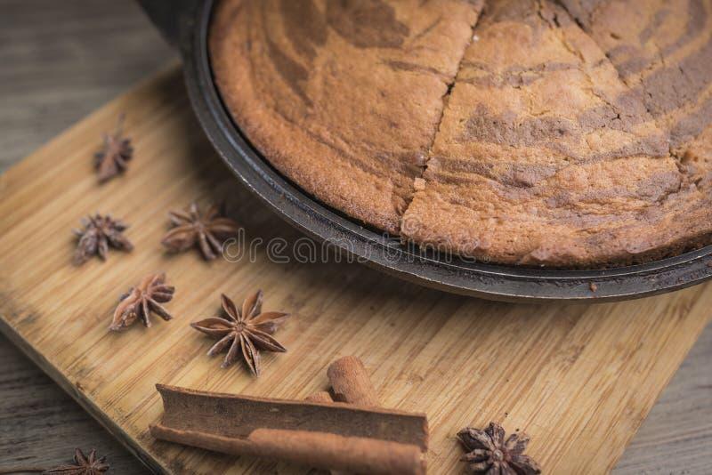 在黑烘烤盘,肉桂条,茴香凝视的自创镶边斑马饼在一个竹切板说谎 免版税库存图片