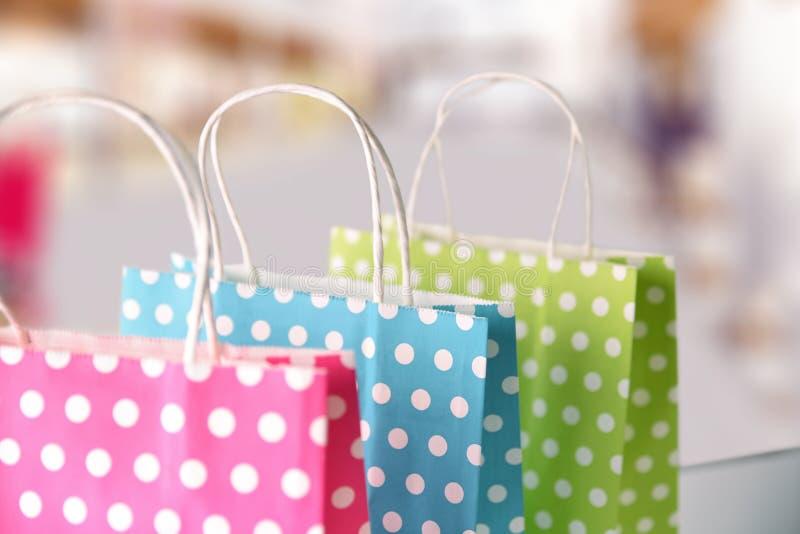 在购物中心的桌上连续上色的三个袋子 免版税库存照片