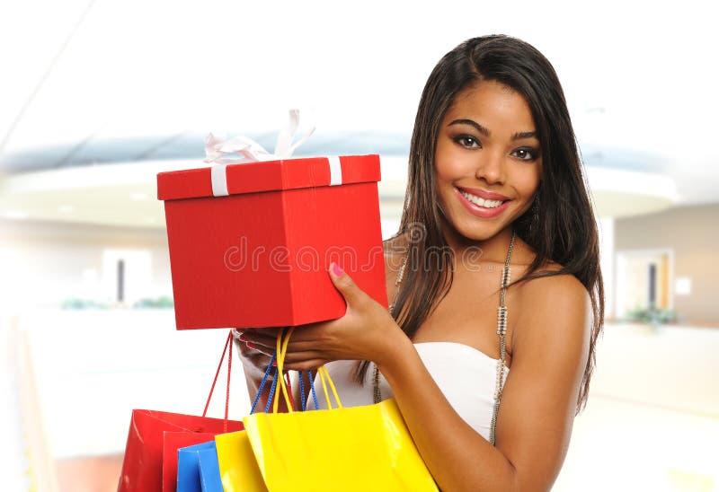 在购物中心里面的年轻黑人妇女 免版税库存照片