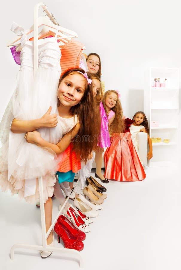 在购物立场期间的小女孩在挂衣架后 库存照片