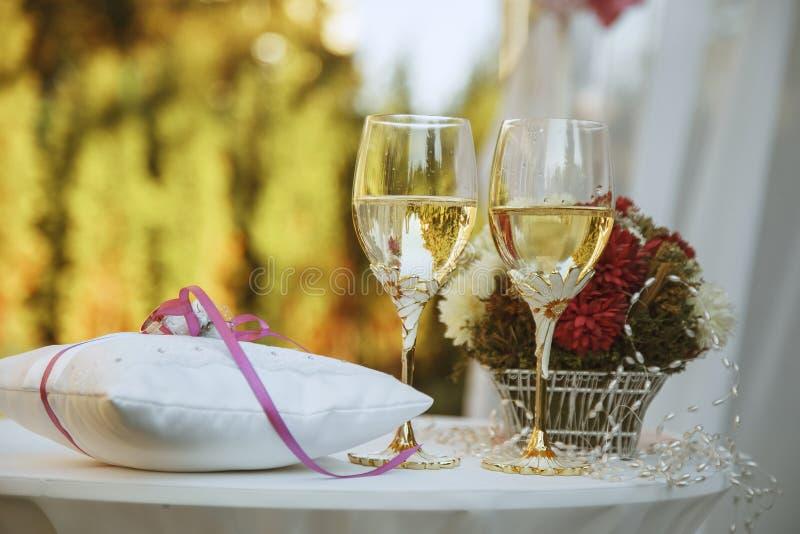 在玻璃和婚戒的香宾在金黄后面的坐垫 免版税库存图片