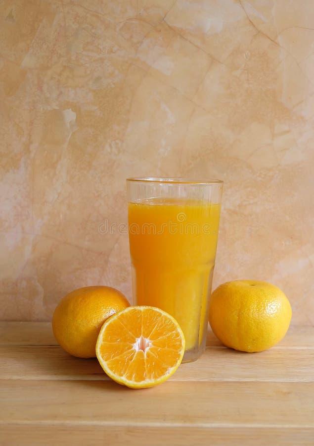 在玻璃和新鲜水果的橙汁在桌上 库存图片