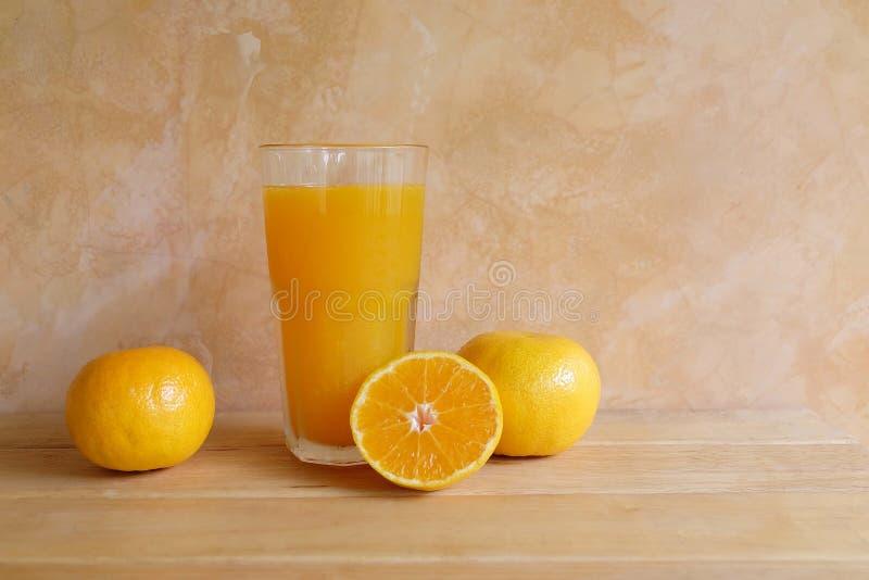在玻璃和新鲜水果的橙汁在桌上 库存照片