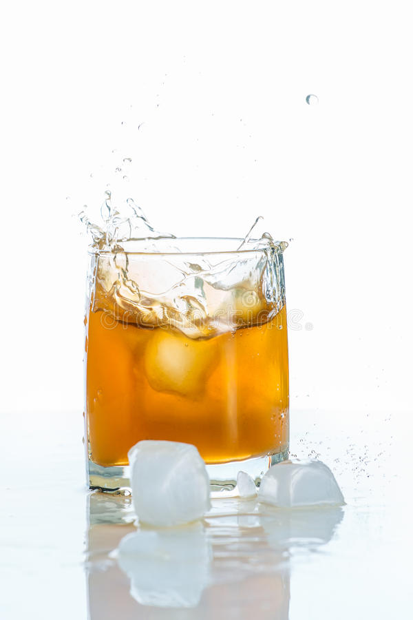 在玻璃和红色水多的苹果的苹果汁与在白色背景的绿色叶子 免版税库存图片