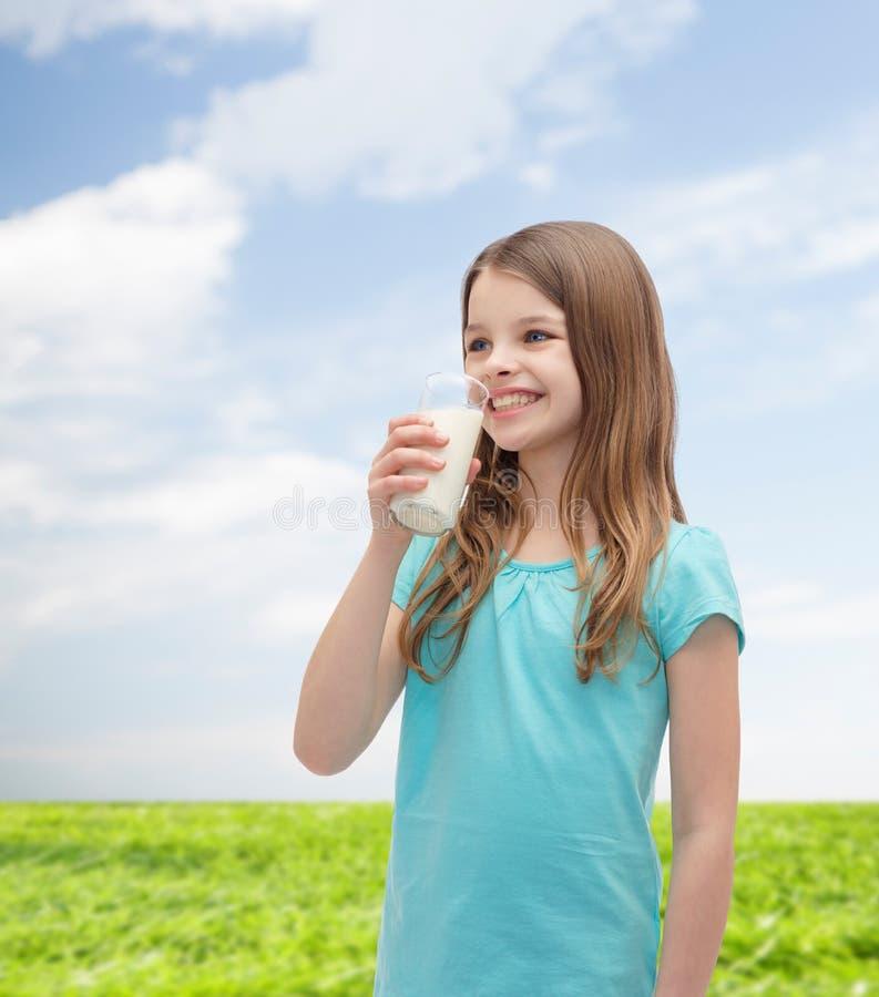 在玻璃外面的微笑的小女孩饮用奶. 藏品, 快乐.
