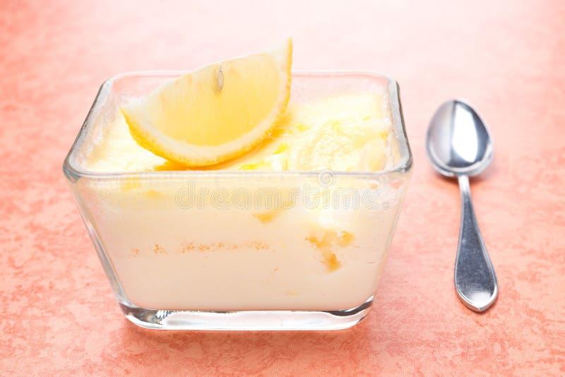 在玻璃形式和匙子的柠檬蛋白牛奶酥 免版税库存照片