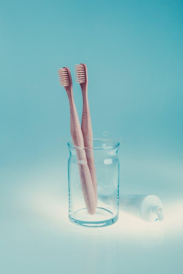 在玻璃杯子的两把米黄牙齿刷子在牙膏在蓝色白色背景的附近 被定调子的照片 库存图片